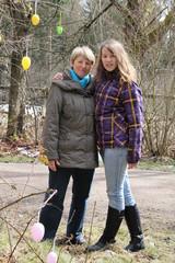 Mädchen macht mit Oma Osterspaziergang im Wald