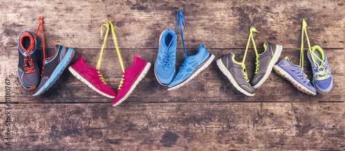 Sports shoes hang on a nail on a wooden fence background - 81180767