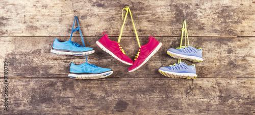 Leinwandbild Motiv Sports shoes hang on a nail on a wooden fence background