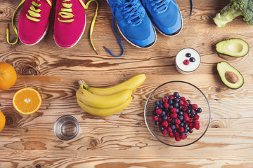 Running shoes and healthy food composition on wooden background