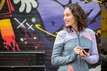 Young attractive woman adjust her music player before running