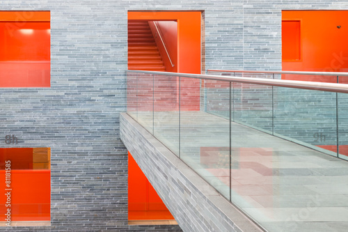 Leinwanddruck Bild Catwalk modern building with floors and orange painted passages