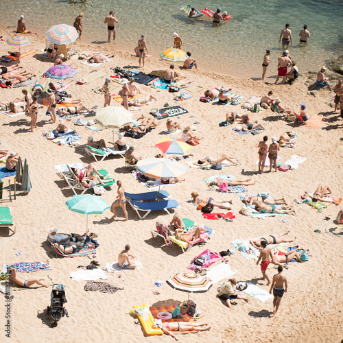 People and sun umbrellas on the beach - 81182351