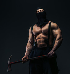 Muscular man in mask holding axe