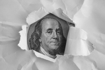 Benjamin Franklin face watching through the torn paper