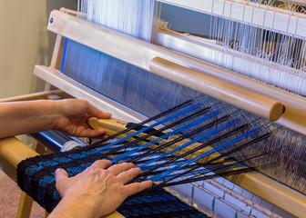 Woman Weaving a Wool Scarf on a Floor Loom