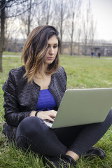 Young girl using a pc laptop computer outdoor in a park
