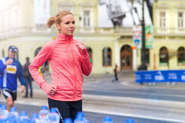 Beautiful young woman running in the city competition with water