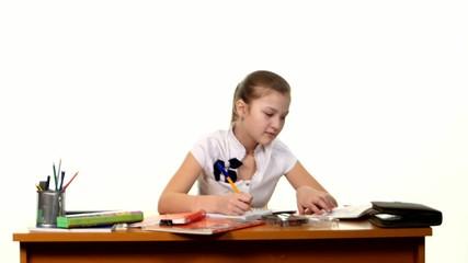 School girl doing her homework and writes essay on white