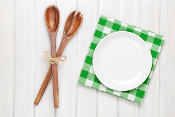 Empty plate and kitchen utensils over wooden table background