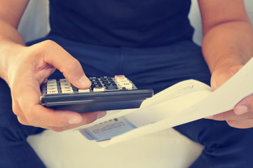 young man checking a bill, a budget or a payroll, filtered