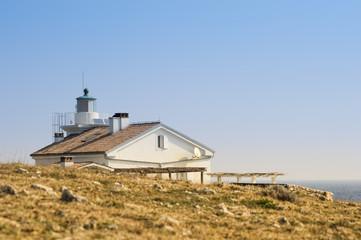 Leuchtturm mit Haus an der Küste