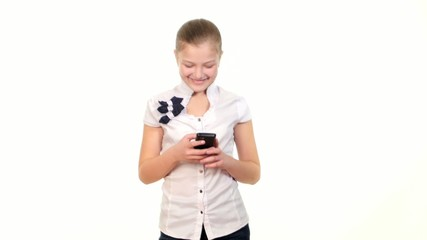 School girl sending message using mobile phone and smiles on