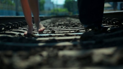 Escaped pair of lovers are walking on the railroad tracks.