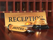 Close-up of room access key and bell on wooden reception desk. S