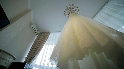 Elegant white wedding dress hanging in the room.