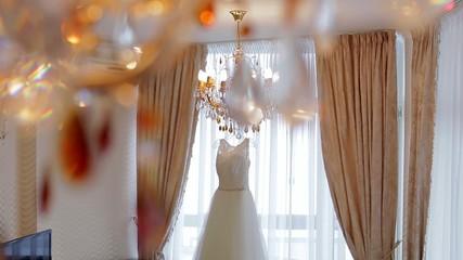 Elegant white wedding dress hanging on a crystal chandelier.