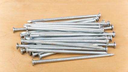 Heap of steel nails on wooden board