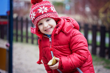 Colorful portrait of cute little boy, eating pear on the playgro