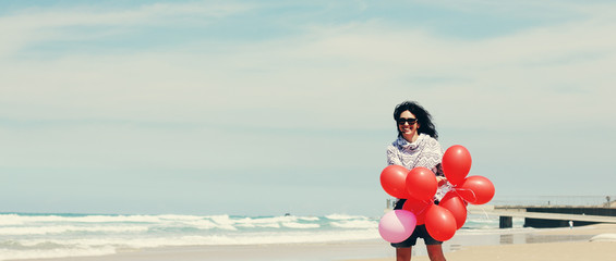 beautiful woman holding red balloons and walking on seaside
