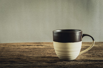 cup of coffee on wooden tabletop against grunge wall