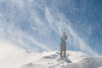 Silhouette of a Female Hiker in a Windy Snow Mountain