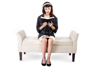 Retro girl sitting on chaise lounge reading a book