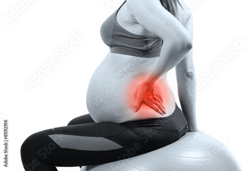 Pregnant woman on gymnastic ball holding her back in pain - 81192914