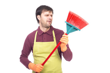 Portrait of lazy young man holding a sweep,conceptual image,