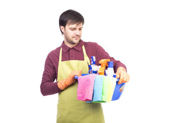 Handsome young man with apron holding cleaning equipment ready t