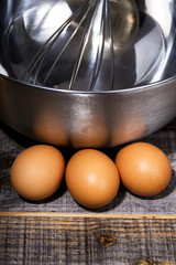 eggs, whisk and bowl on wooden table