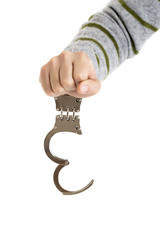 Closeup of unlocked handcuffs hanging on man hand