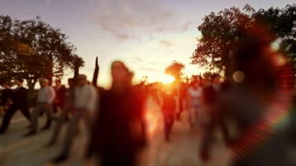 Crowd walking at sunset, camera flying