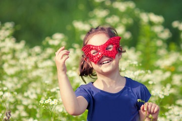 Happy little girl wearing a red mask on the flower meadow