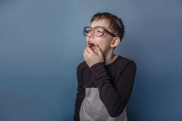 European-looking  boy of ten years in  glasses yawning on gray b