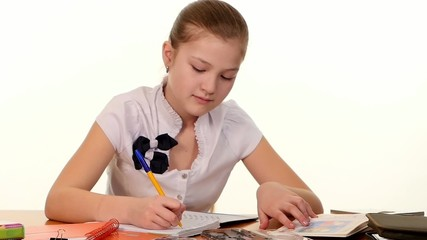 School girl doing her homework and writes essay on white