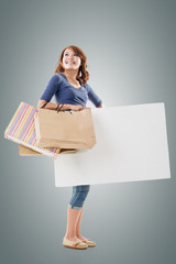 Shopping woman holding bags and blank board