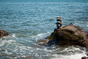 Stacked Pebble Tower being Washed by Wave