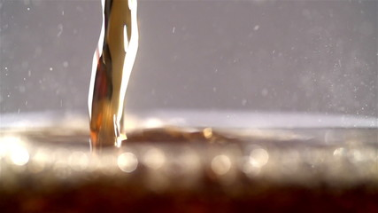 Cola carbonated drink pouring in glass with splash. Slow motion