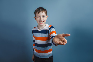 European-looking boy of ten years pulls his hand requests on a g