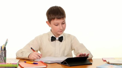 Clever school boy taught lessons using the tablet computer doing