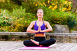 Woman training yoga outdoor in autumn or fall park
