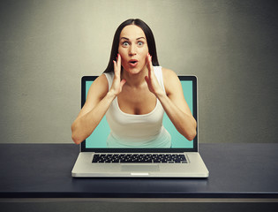 amazed woman got out of the laptop