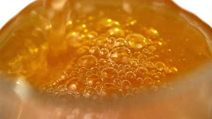 Orange Soda Pouring with bubbles into Glass.