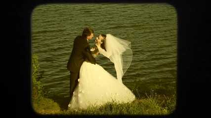 Happy Newlyweds Near Lake At Wedding Day