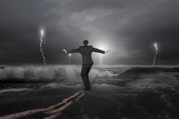 Businessman balancing on old iron chain with dark stormy ocean
