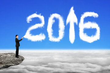 Businessman spraying white 2016 year cloud shape in sky cloudsca