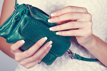 Female hands with manicure with green handbag