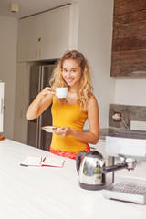 pretty woman sitting alone in a kitchen and drinking her morning