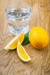 glass of water and sliced fresh lemon on wooden background